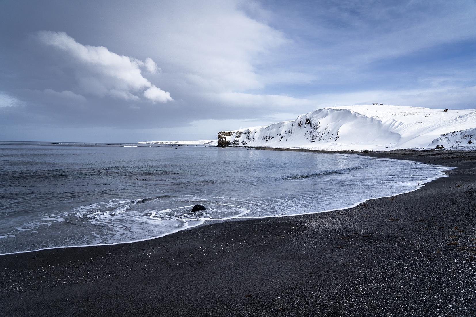 plage de sable noir falaises ciel bleu nuages Islande du Nord