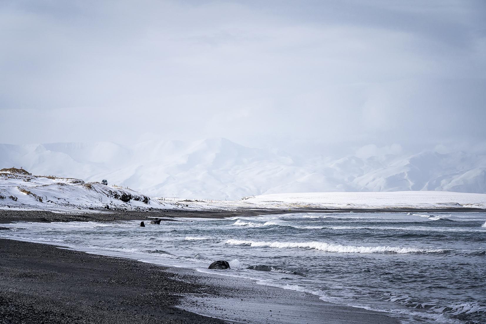 plage de sable noir montagnes mer neige