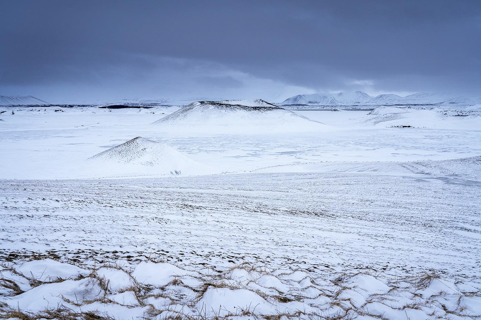 lac gelé volcans Mývatn Skútustaðagígar Islande du Nord nuages noirs neige