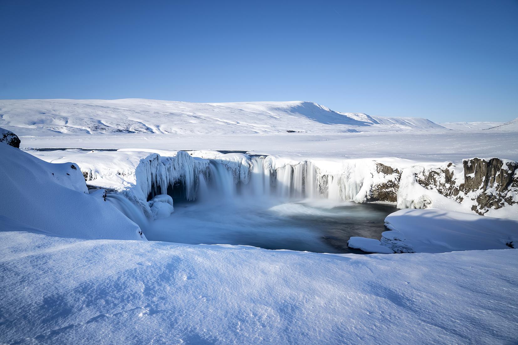 Islande du Nord Goðafoss vue d'ensemble cascade féerique neige eau stalactites ciel bleu