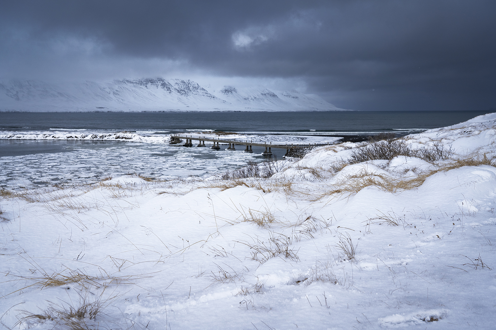 Skagafjördur Islande du Nord ponton montagnes mer neige nuages noirs