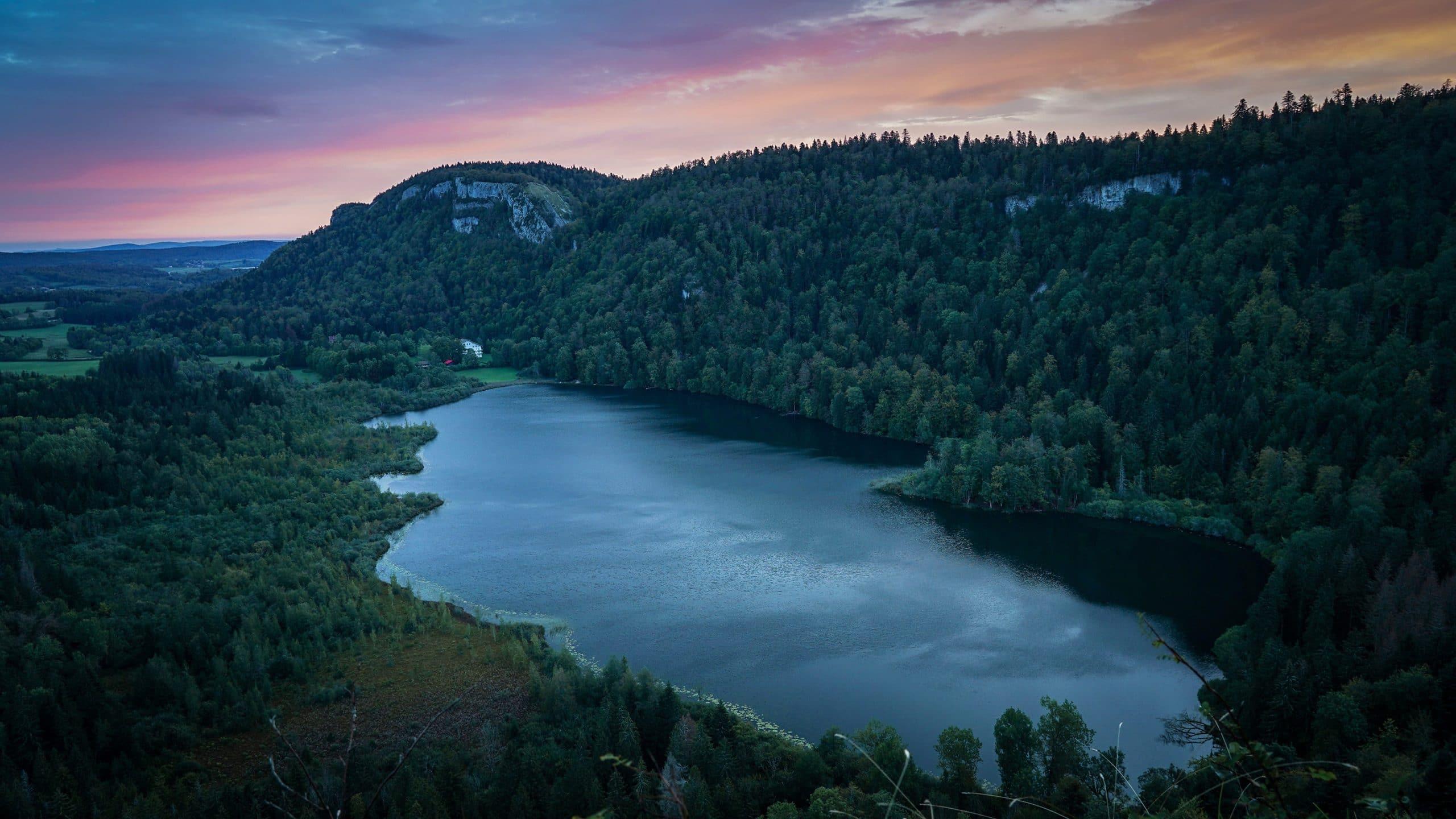 lac de Bonlieu lever de soleil eau nuages roses oranges Jura sapins montagnes