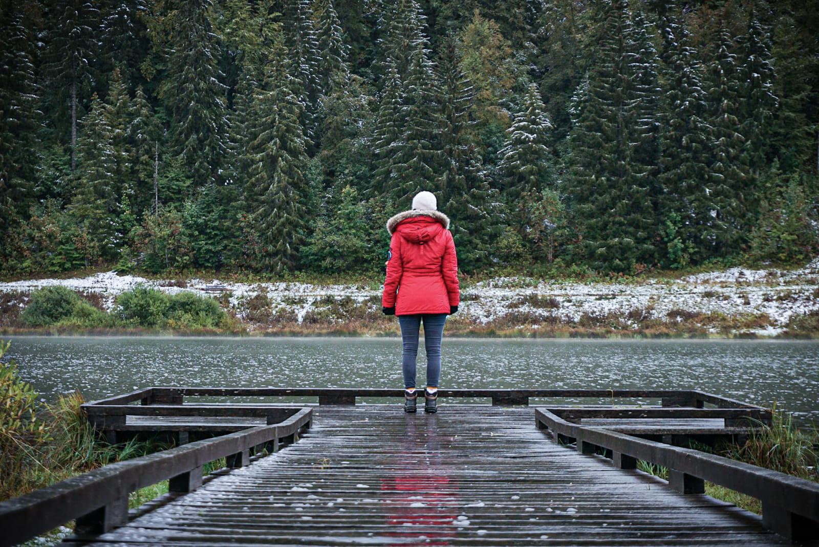Jura lac Lamoura ponton bois sapins neige personne manteau rouge