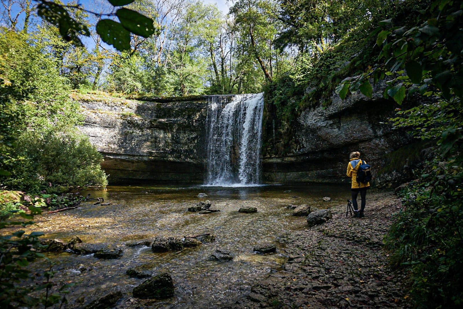 cascade du Hérisson eau lykorne ciré jaune soleil ciel bleu forêt Jura