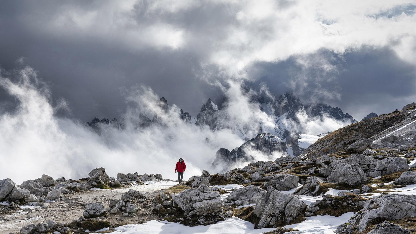 Tre Cime di Lavaredo italie homme manteau rouge marche montagnes nuages