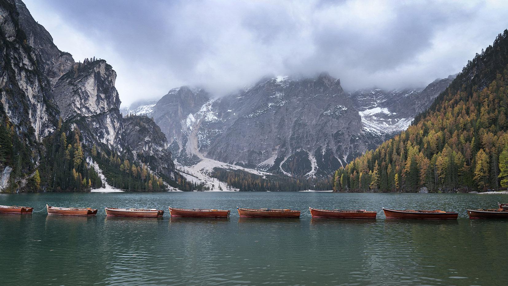 Barques file indienne eau lago di Braies Dolomites sapins montagnes nuages